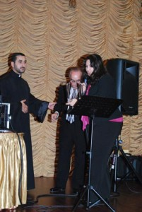 Father Mkhitar is receiving a recognition plaque from AAEF